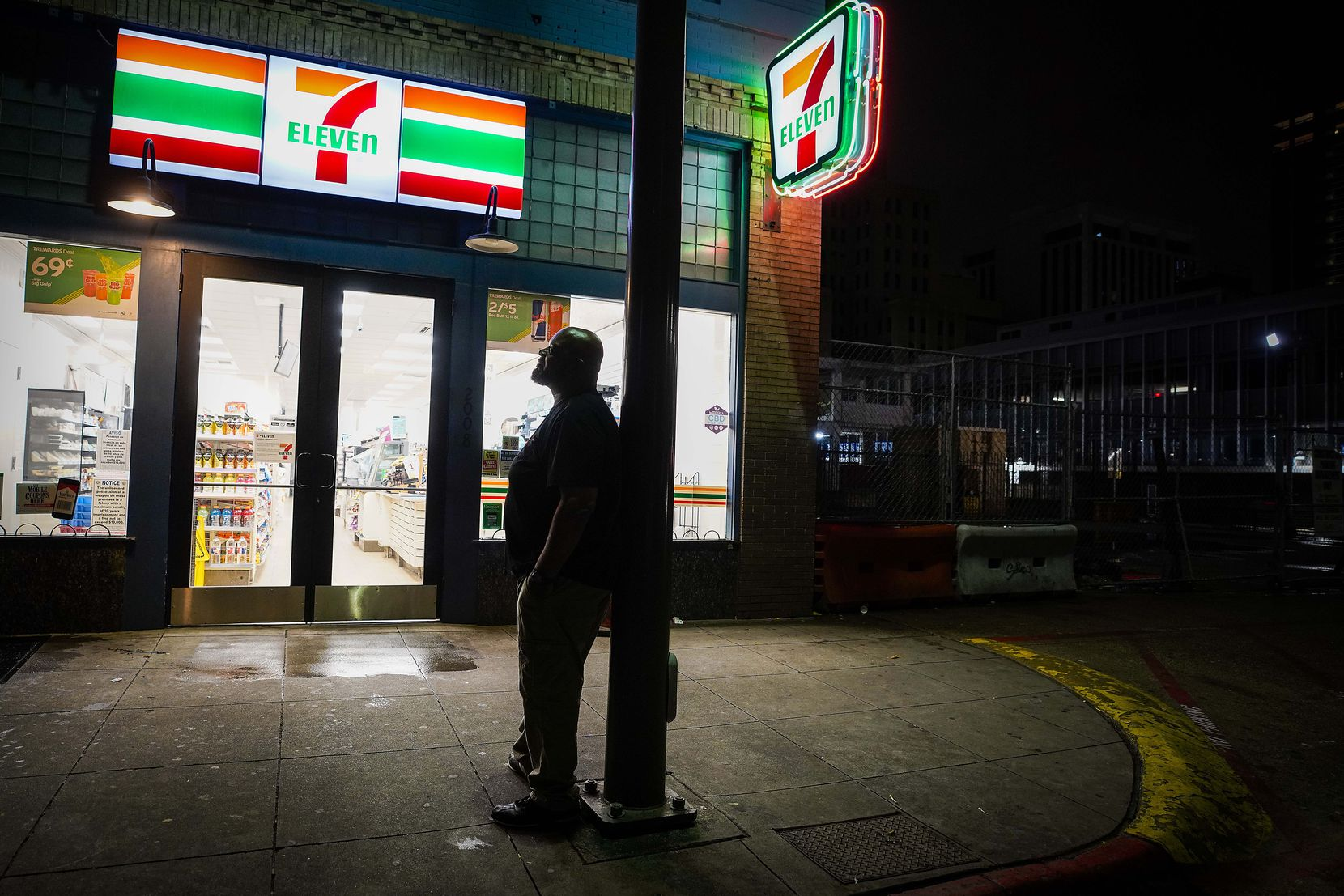 Mark Anthony Jenkins looks out over the completely empty Commerce Street in front of the 7-Eleven store where he works in downtown Dallas at around 12:45 a.m. on Tuesday, March 24, 2020.