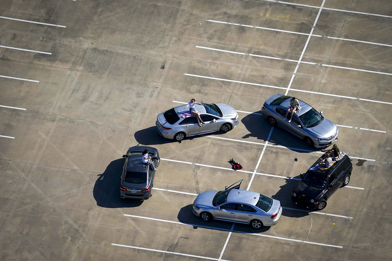 Practicing their own form of social distancing, young people gather in the parking lot of McKinney High School on Tuesday, March 24, 2020.