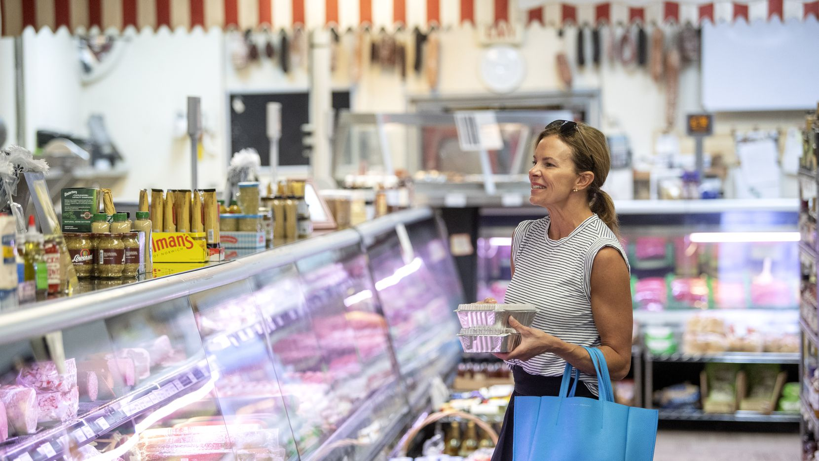 Kristi Pierce of University Park checked out the meat counter at Kuby's Sausage House and European Market on March 24 in Dallas. While Kuby's temporarily closed its restaurant, it kept the market half of the store open for neighbors in search of staples like fresh produce, milk and even toilet paper.