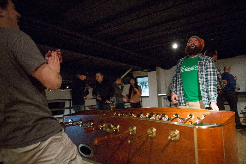 Chris Leurig (right) and Jacob Peraza (left) laugh after playing foosball at Peticolas Brewing Company in Dallas, Texas, on Thursday, January 12, 2017.