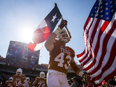 University of Texas tight end Logan Mills carried the Texas flag as he led the team onto the field before the 2015 Red River Showdown.