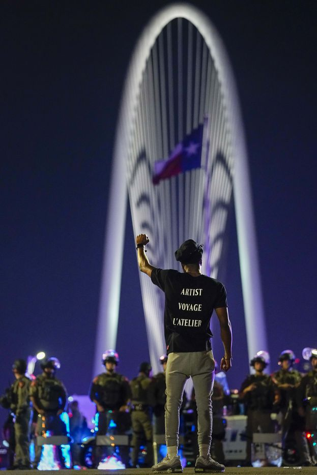 Demonstrator Devante Williamson stands in the middle of the street in solidarity as law enforcement officers blocking the western side of the Margaret Hunt Hill Bridge while police conduct mass arrests after protesters demonstrating against police brutality marched onto the bridge on Monday, June 1, 2020, in Dallas. Protests continued Monday, a week after the death of George Floyd.