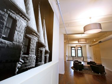 A common area is pictured on the second floor in the old David Crockett School that's been turned into The Principal, Landmark Luxury Residences on Carroll Avenue in Dallas Monday, August 13, 2018. Large images of Dallas landmarks printed on canvas decorate the space. Local photographer Jim Olvera was commissioned for the work. (Guy Reynolds/The Dallas Morning News)