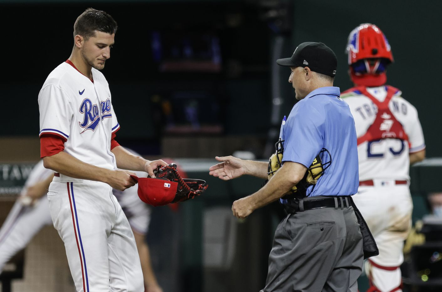 Home plate umpire Dan Iassogna inspects Texas Rangers relief pitcher Brett Martin's (59) glove and hat during the seventh inning of a baseball game against the Oakland Athletics in Arlington, Monday, June 21, 2021. (Brandon Wade/Special Contributor)