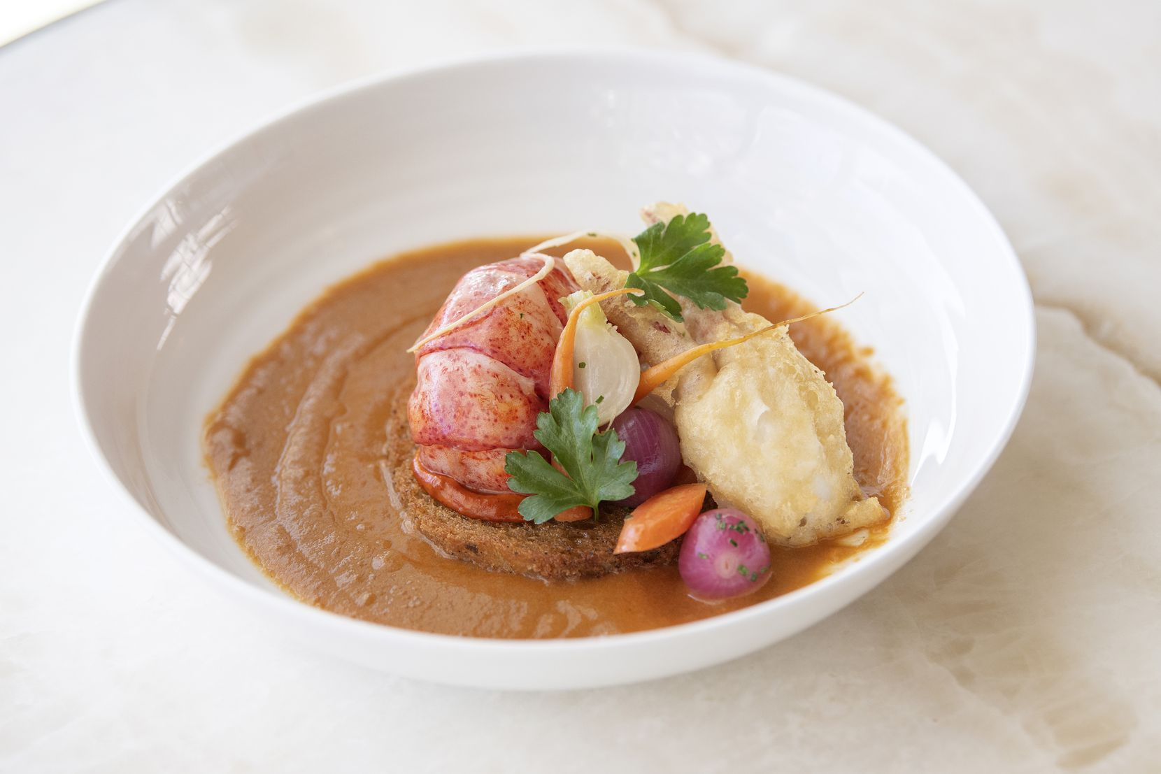 Bisque de Homard is served at Bullion, Feb. 6, 2020, in downtown Dallas. The dish includes a Lobster bisque, brioche croutons, lobster tempura and a saffron aioli.