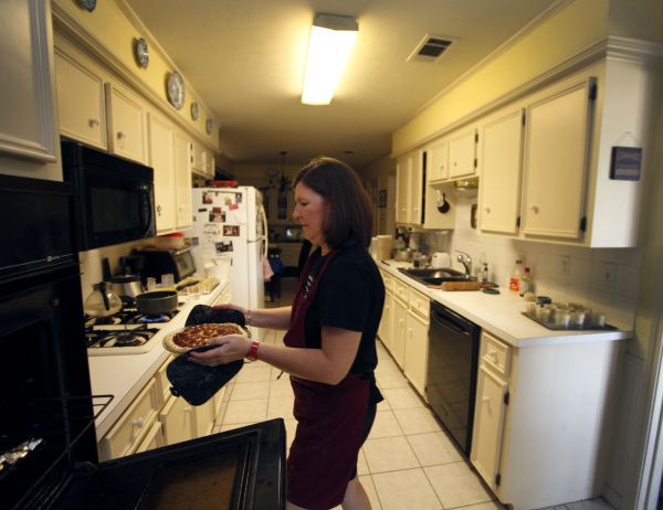 Karen Kern places miniature pies in jars in her Garland home. She lost her catering job last month and launched Pies for Pete's Sake, which she already finds more fulfilling than her former job.