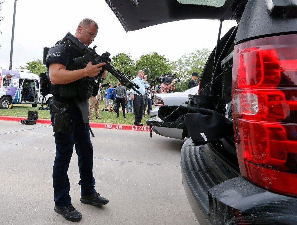An Irving police officer checks his rifle as he arrives at the shooting scene.