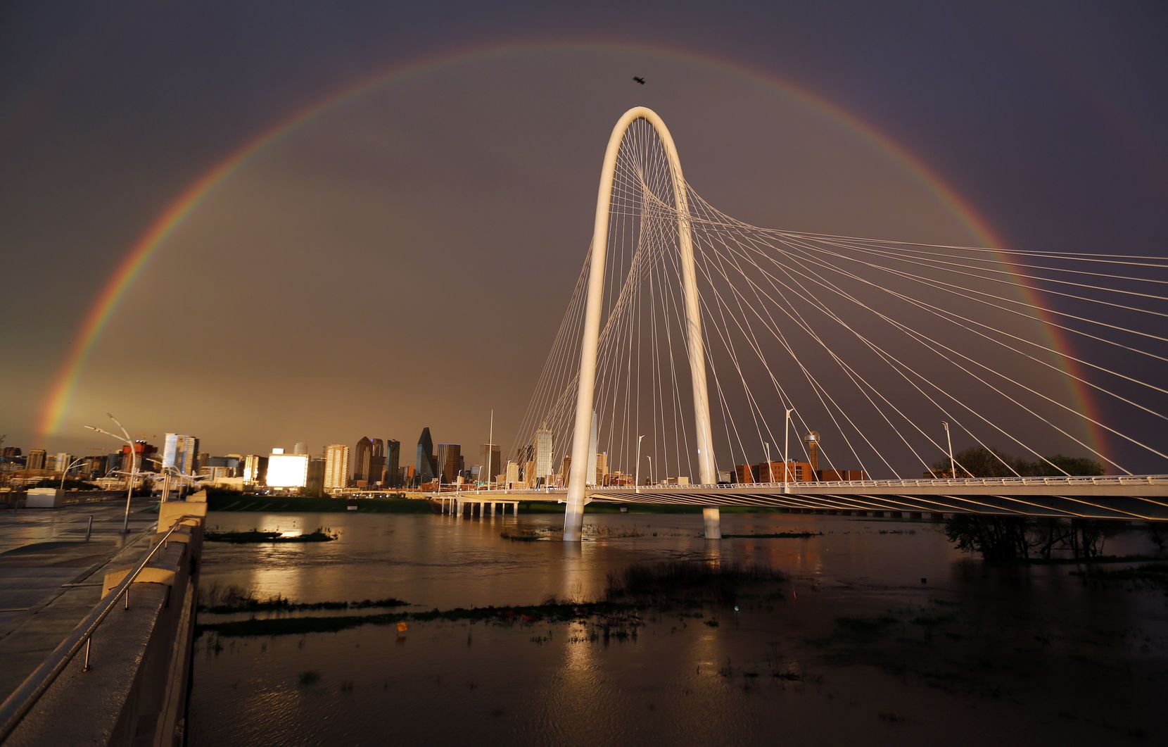 A full rainbow spans downtown Dallas, the rain-filled Trinity River and the Margaret Hunt Hill Bridge, Thursday March 19, 2020.