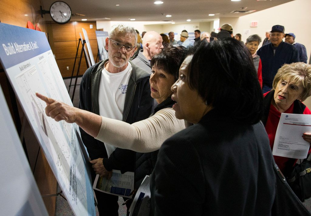 Pam Wilemon, center, points to a map of possible build alternatives during an open house for people to view plans and talk to company and corporate officials about a $15 billion Dallas to Houston high-speed rail line on Monday at Wilmer-Hutchins High School in Dallas. At left of Wilemon is Robert Thomson, and at right is Amy Moore. (Ashley Landis/The Dallas Morning News)