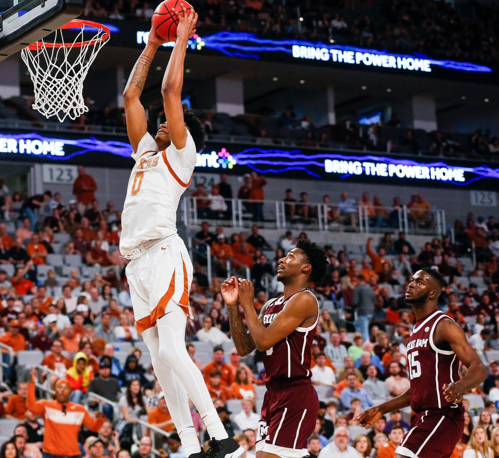 Texas Longhorns forward Gerald Liddell (0) dunks over Texas A&M Aggies guard Quenton Jackson (3) and forward Jonathan Aku (15) during the first half of a basketball matchup between the Texas Longhorns and Texas A&M Aggies in the Lone Star Showdown on Sunday, Dec. 8, 2019 at Dickies Arena in Fort Worth, Texas. (Ryan Michalesko/The Dallas Morning News)