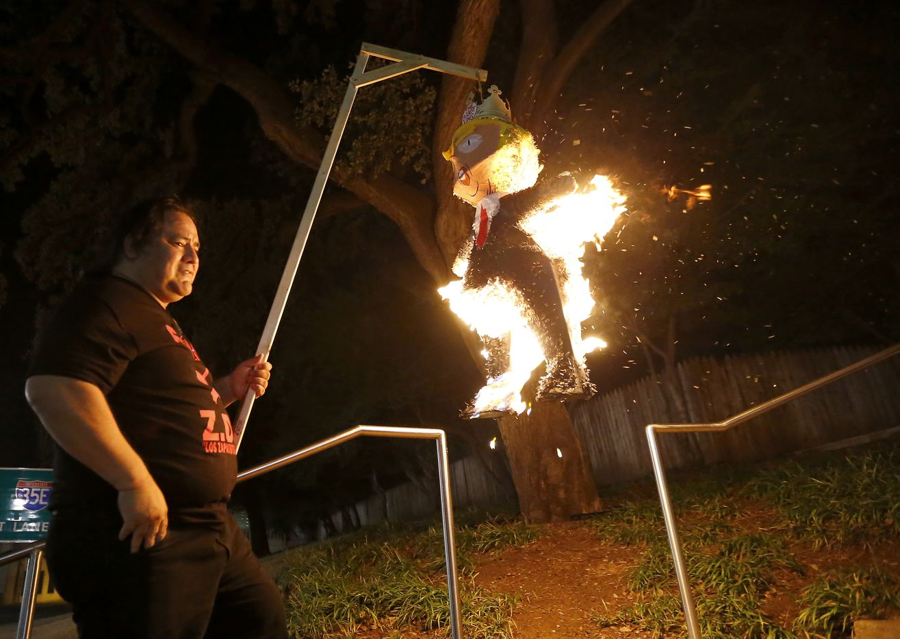 Leroy Peña holds a burning President Donald Trump pinata during a rally organized by the community group Resistance at Dealey Plaza in Dallas, Friday, Jan. 20, 2017.