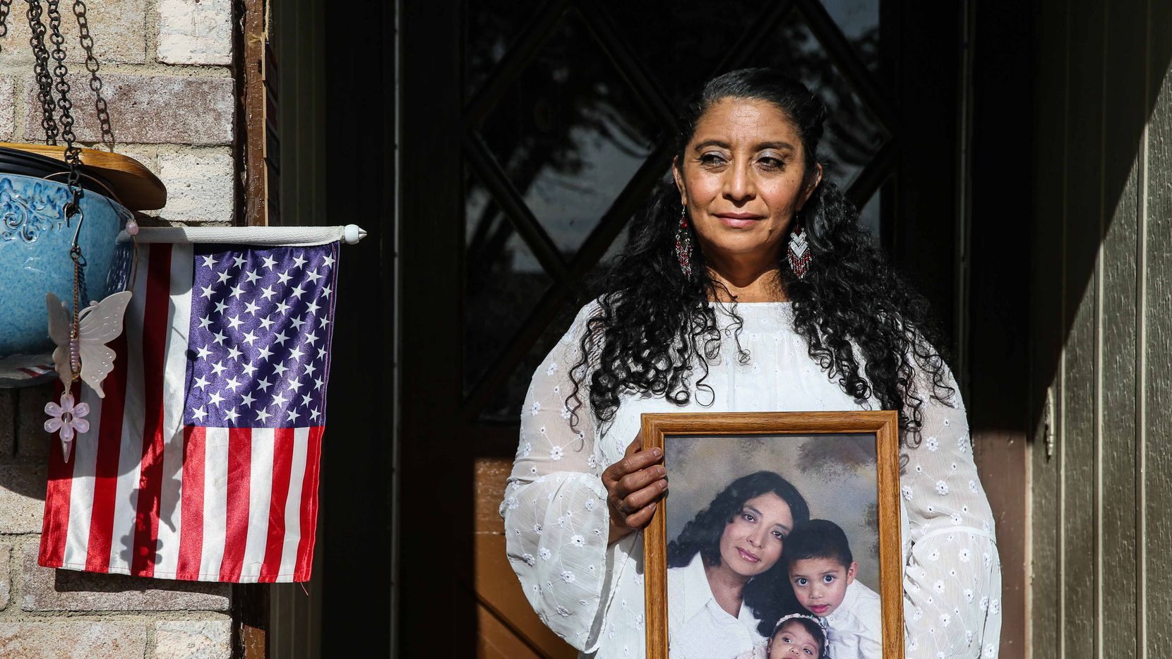 Dalila Sandoval poses in front of her home holding a photo of her and her two U.S.-born children in Arlington on Wednesday, December 23, 2020. Sandoval has been in immigration limbo for nearly two decades as a Tepesiana, as she calls herself, an immigrant who holds a temporary protected status in the U.S.. The 52-year-old native of El Salvador is pushing for permanent residency and a citizenship pathway for all immigrants holding TPS.