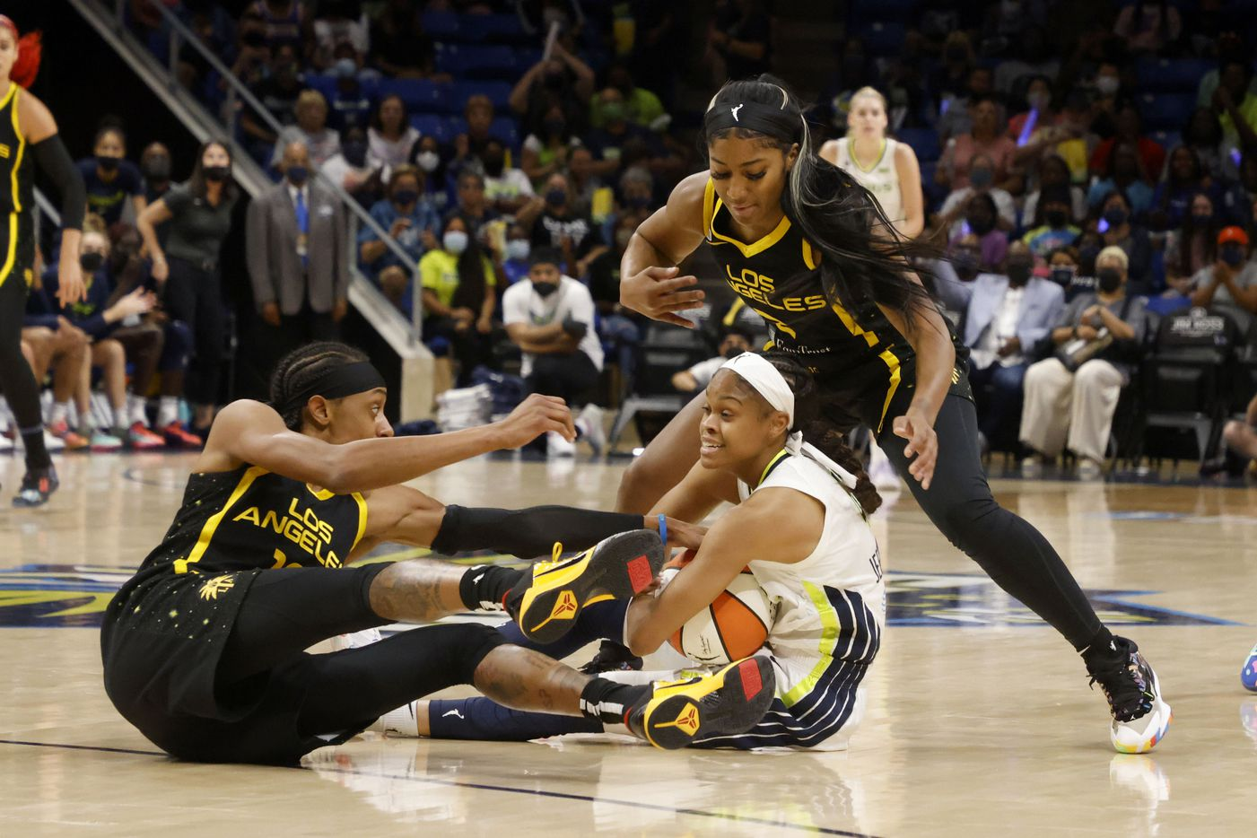 Dallas Wings guard Moriah Jefferson (4) tries to keep the ball away from Los Angeles Sparks guard Brittney Sykes, left, and guard Te'a Cooper, right, during the first half of a WNBA basketball game in Arlington, Texas on Sunday, Sept. 19, 2021. (Michael Ainsworth/Special Contributor)