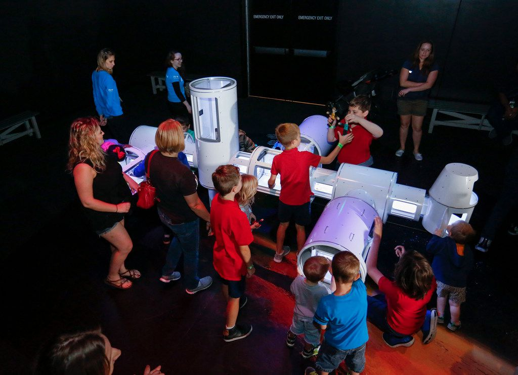 Children and adults get to play with a hands-on model resembling the International Space Station at the Perot Museum of Nature and Science media preview of the Journey To Space exhibit Thursday, October 18, 2017. The bilingual exhibit will be at the museum till May 6, 2018.