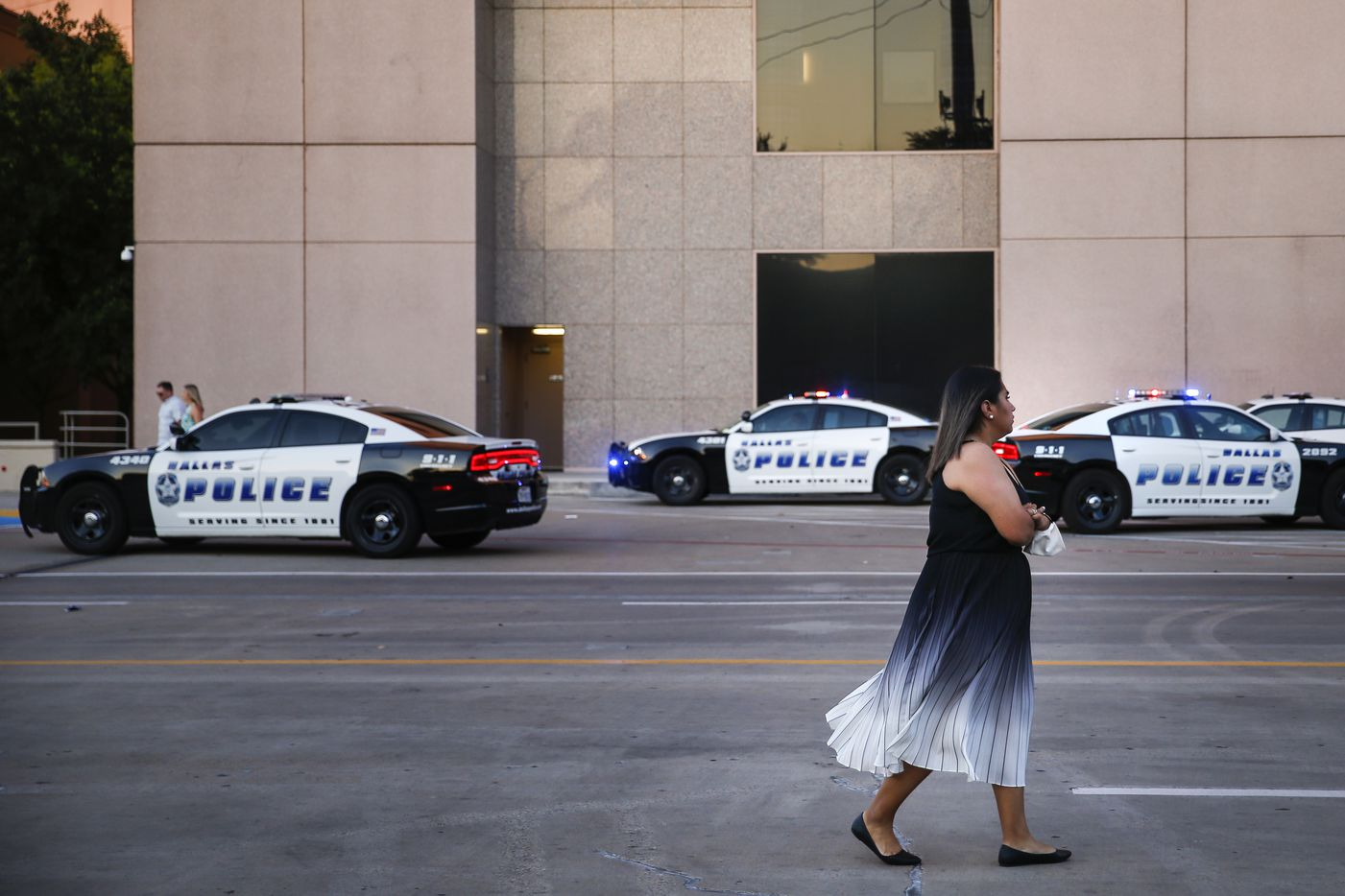 """A store employee, who wished to remain anonymous, waits outside to collect her belongings at Galleria Dallas mall, where a shooting was reported Tuesday, June 16, 2020 in Dallas. """"It happened all the sudden,"""" she said of what she witness from near the mall's Apple Store. """"We were getting ready to close and we heard a loud boom. Then we heard like ten shots so we rushed to our back room. You could hear it so clear, like just a ton of books falling."""""""
