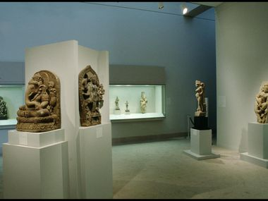 "A Lakshmi-Narayana stele from Nepal (foreground, center left) is shown on display in the exhibition ""East Meets West: Sculpture from the David T. Owsley Collection"" from 1993 to 1994 at the Dallas Museum of Art. The DMA removed the stele from display in late 2019 in response to concerns about the provenance of the artwork."