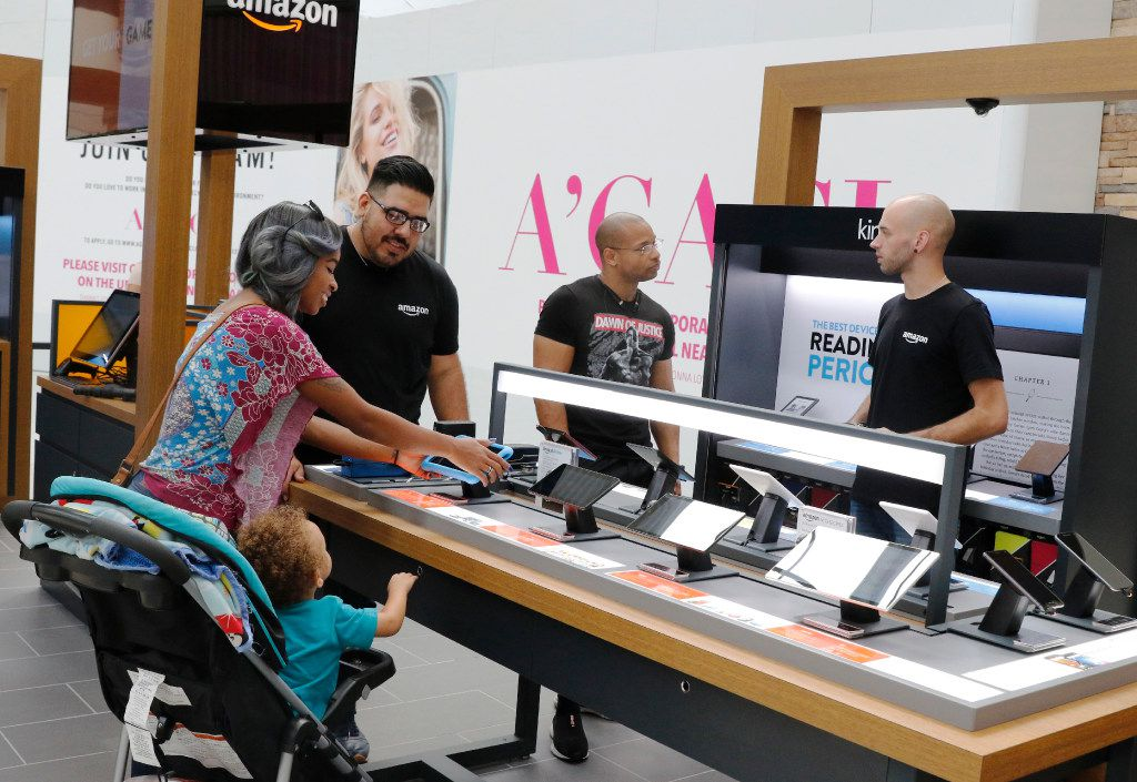 Presley Edwards and Paxton, 2, left, of Arlington, get help from Justin Maldonado, Retail Experience Associate while Alec Hall; Retail Experience Manager, right, helps Theland Edwards, (3rd from left) at Amazon.com Pop-up store located on the first level at the Parks Mall at Arlington, Texas on Wednesday, September 14, 2016. The store opened August 21, 2016. (David Woo/The Dallas Morning News)