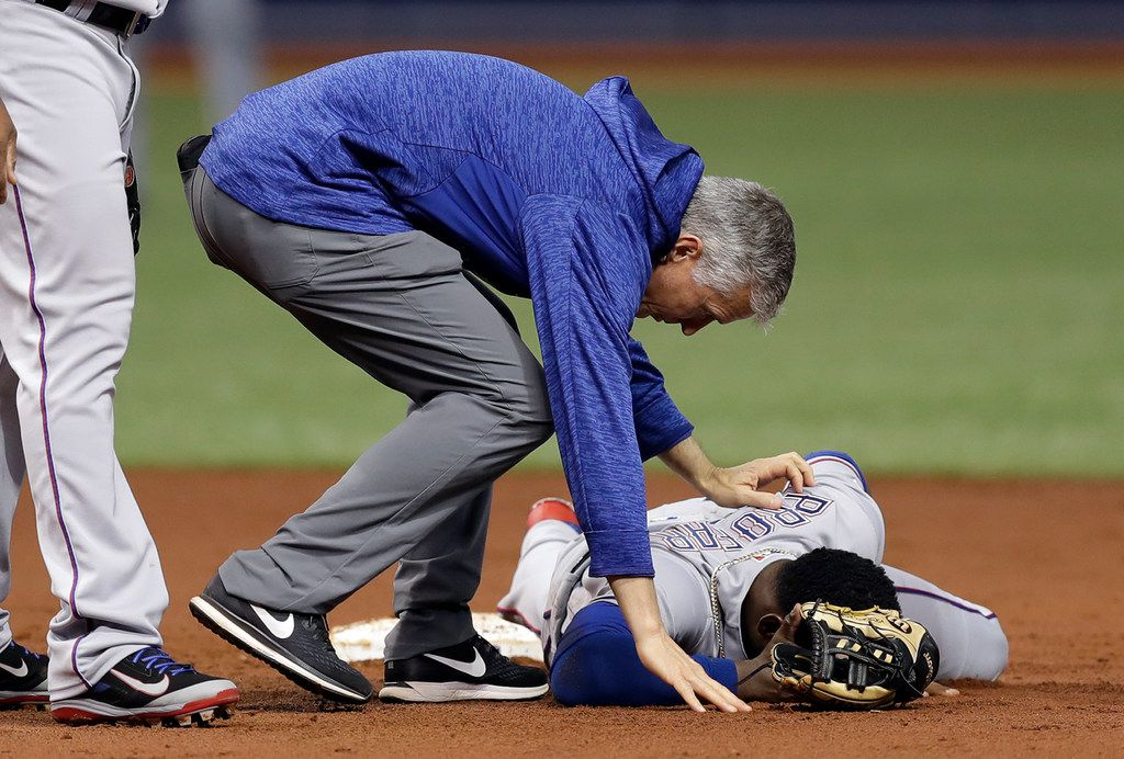 Texas Rangers trainer Kevin Harmon helps shortstop Jurickson Profar after he was injured in a collision with Tampa Bay Rays' Mallex Smith during the second inning of a baseball game Monday, April 16, 2018, in St. Petersburg, Fla. Profar left the game. (AP Photo/Chris O'Meara)
