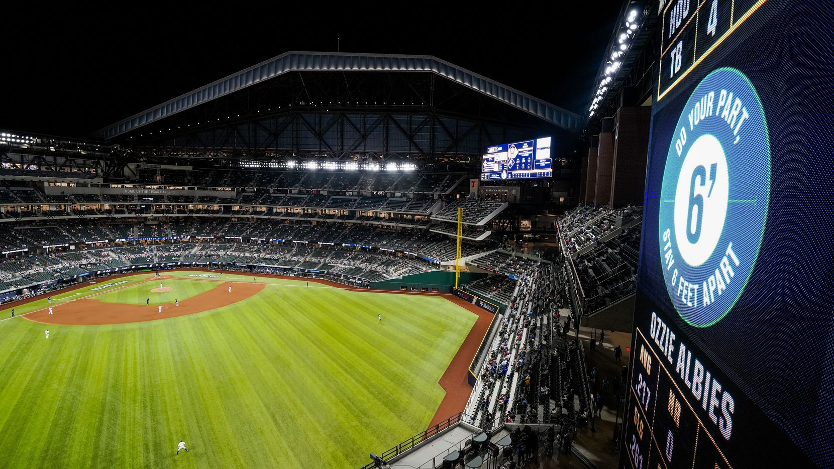 A scoreboard sign in center field encourages social distancing during the eighth inning in Game 1 of a National League Championship Series between the Los Angeles Dodgers and the Atlanta Braves at Globe Life Field on Monday, Oct. 12, 2020.