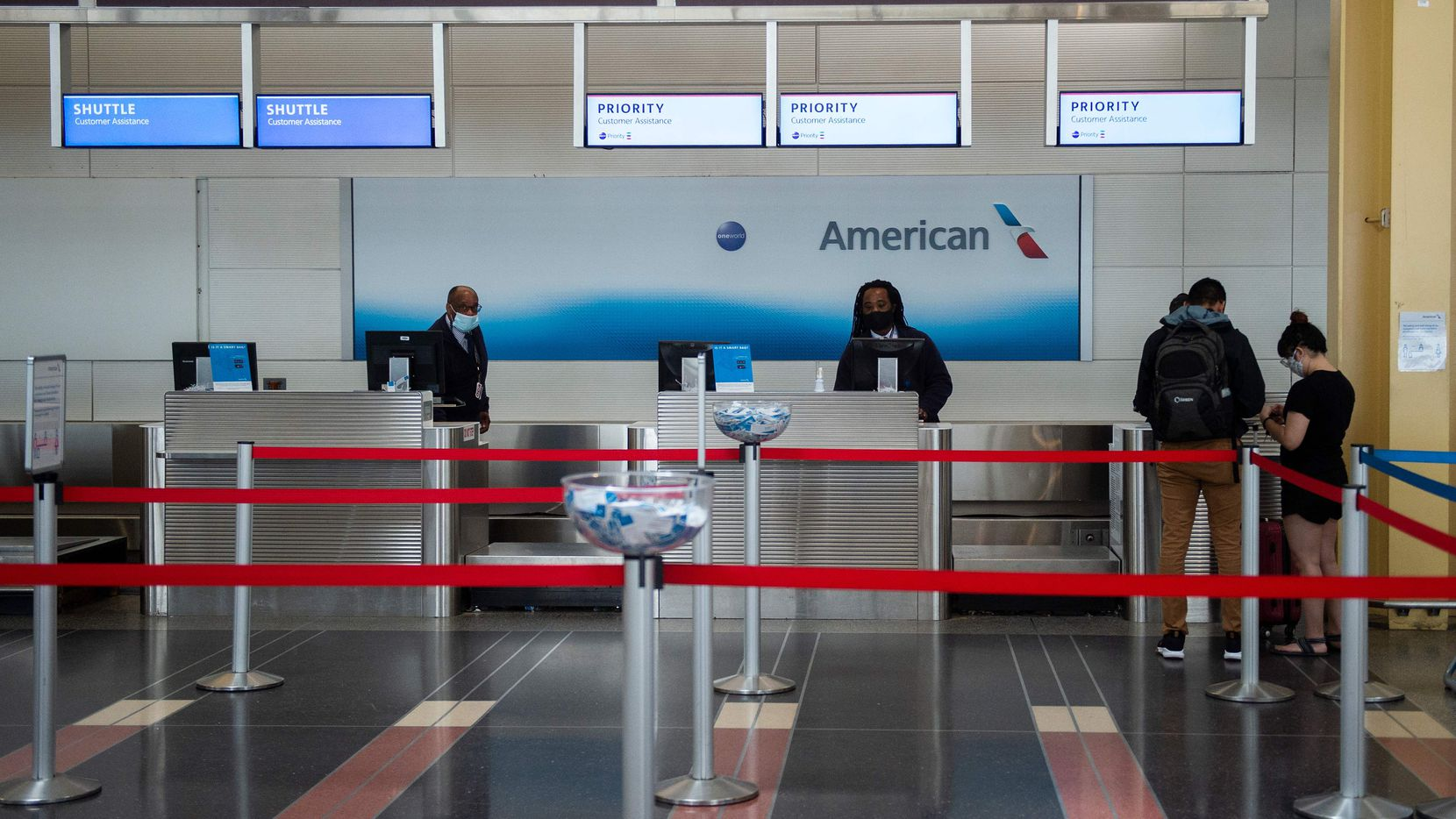American Airlines employees check in two passengers at a mostly empty check-in counter in Ronald Reagan Washington National Airport in Arlington, Virginia, on May 12, 2020. - The airline industry has been hit hard by the COVID-19 pandemic, with the number of people flying having decreased by more than 90 percent since the beginning of March. (Photo by ANDREW CABALLERO-REYNOLDS / AFP) (Photo by ANDREW CABALLERO-REYNOLDS/AFP via Getty Images)