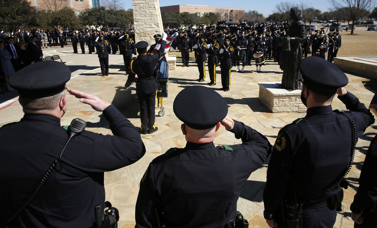 Dallas Police salute as the U.S. flag is removed from the casket following a funeral service for Dallas Police officer Mitchell Penton at Prestonwood Baptist Church in Plano, Monday, February 22, 2021. Penton was killed Saturday, Feb. 13, 2021, in a crash involving a drunk driving suspect. (Tom Fox/The Dallas Morning News/Pool)