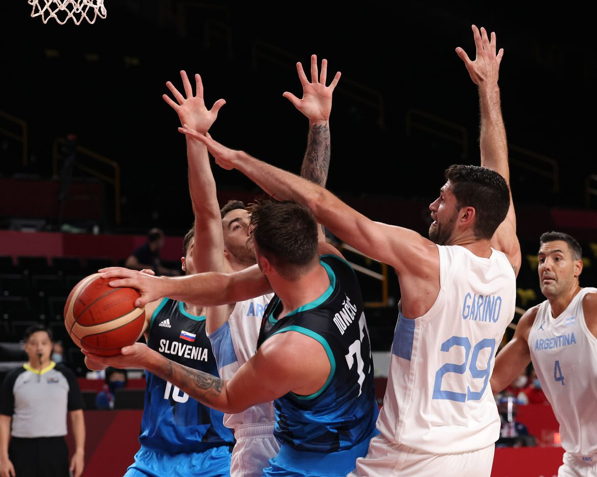 Slovenia's Luka Doncic (77) passes to Mike Tobey (10) out of a double team from Argentina's Luca Vildoza (17) and Patricio Garino (29) in the first half of play during the postponed 2020 Tokyo Olympics at Saitama Super Arena on Monday, July 26, 2021, in Saitama, Japan. Slovenia defeated Argentina 118-100. (Vernon Bryant/The Dallas Morning News)