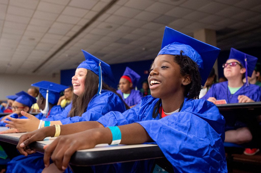 Jaiden, 10, (right) and Jessica, 11, (left) watch a magic show during a graduation ceremony for Kids' University, an educational summer camp put on by Rainbow Days, which serves local homeless children, on Friday, June 7, 2019 at The University of Texas at Dallas in Richardson, Texas.