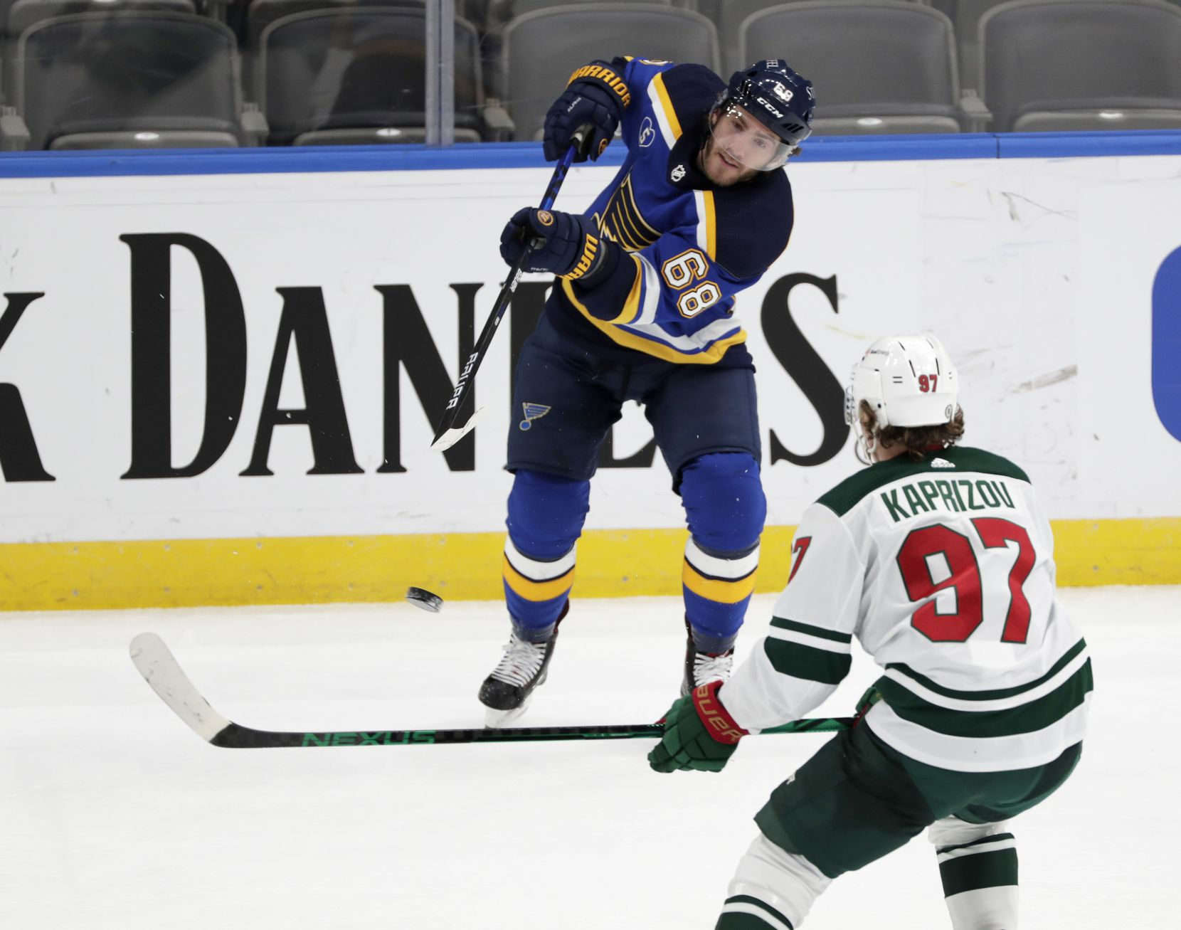 St. Louis Blues' Mike Hoffman (68) flips the puck past Minnesota Wild's Kirill Kaprizov (97) in the third period of an NHL hockey game, Wednesday, May 12, 2021 in St. Louis. The Blues beat the Wild 4-0.