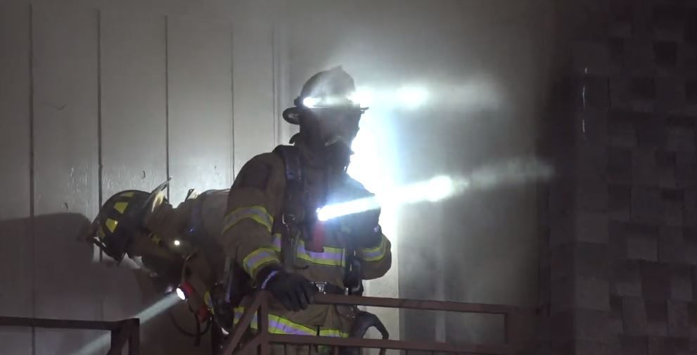 Firefighters emerge from a smoke-filled apartment unit Tuesday morning in Euless.