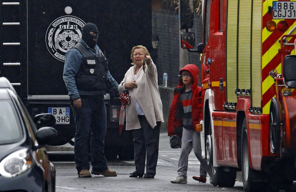 In this March 22, 2012 file photo, a woman speaks with a police officer near a building where the chief suspect in an al-Qaeda-linked killing spree is holed up in an apartment in Toulouse, southern France. To stop the stream of French youths pursuing jihad in Syria, France is preparing to do something it has never done before: tackle terrorism at its roots before it starts, by involving schools, parents and local Muslim leaders, The Associated Press has learned. Memories are still fresh of the radical Islamic Frenchman who gunned down children at a Toulouse Jewish school in 2012, after training in Afghanistan and Pakistan.