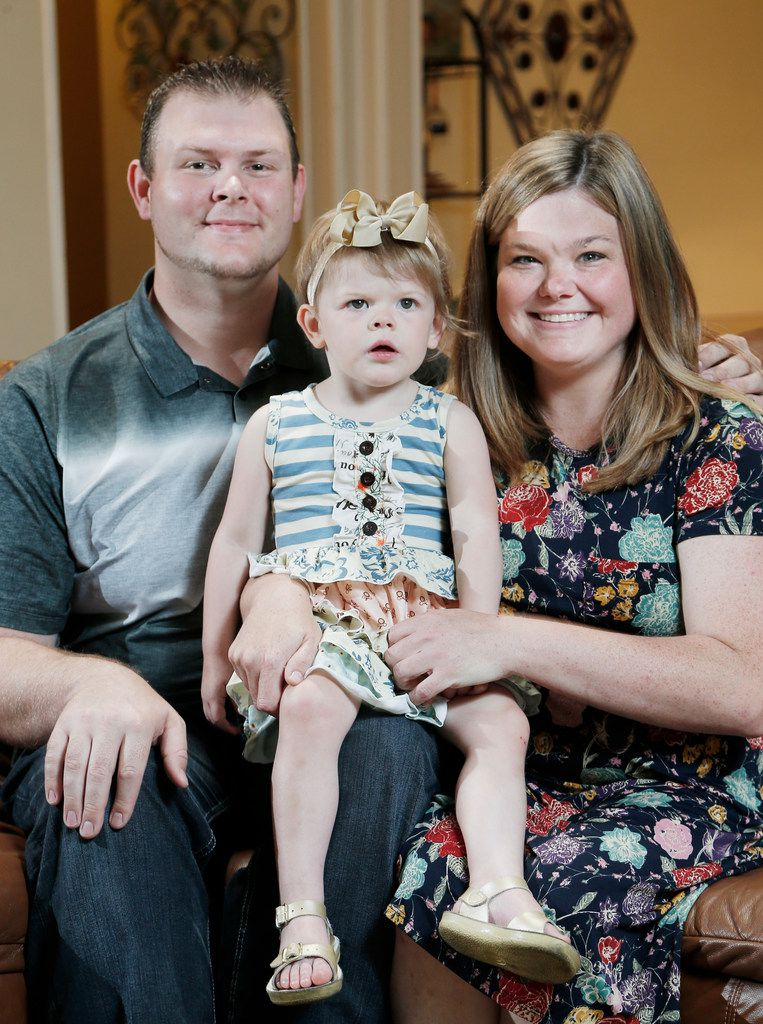 Marshall and Jessica Hitt and their daughter, Olivia, 2, sit for a portrait at their home in Arlington.  As Jessica's health rapidly deteriorated, her husband, Marshall, rushed her back to the hospital, where she had given birth just four days earlier.