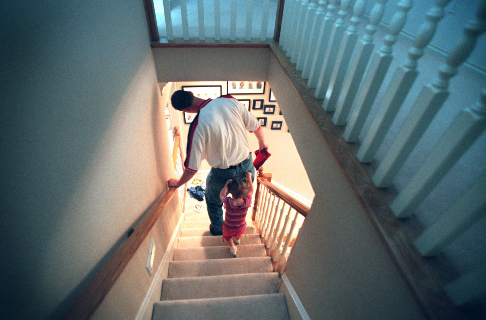 Dallas Mavericks center Shawn Bradley (7-foot-6) has to duck to clear door frames and stairway ceilings in his own home.  Here he leans over to fit in the stairwell as he is followed downstairs by daughter Chelsea, 3.