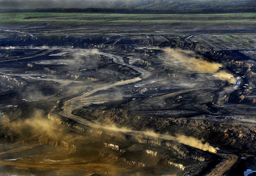 Dust rises from the Alberta, Canada, oil sands project of Syncrude, which is partly owned by Imperial, Exxon's Canadian affiliate.