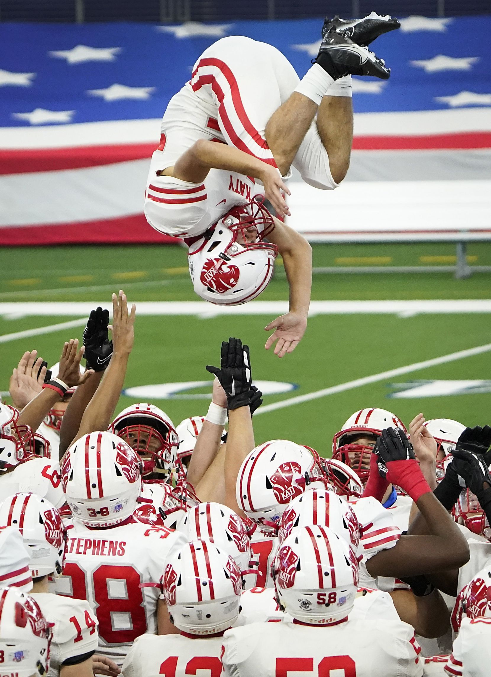 Katy defensive back Colton Cable (32) flips over his teammates as the team takes the field for the Class 6A Division II state football championship  game against Cedar Hill at AT&T Stadium on Saturday, Jan. 16, 2021, in Arlington, Texas.