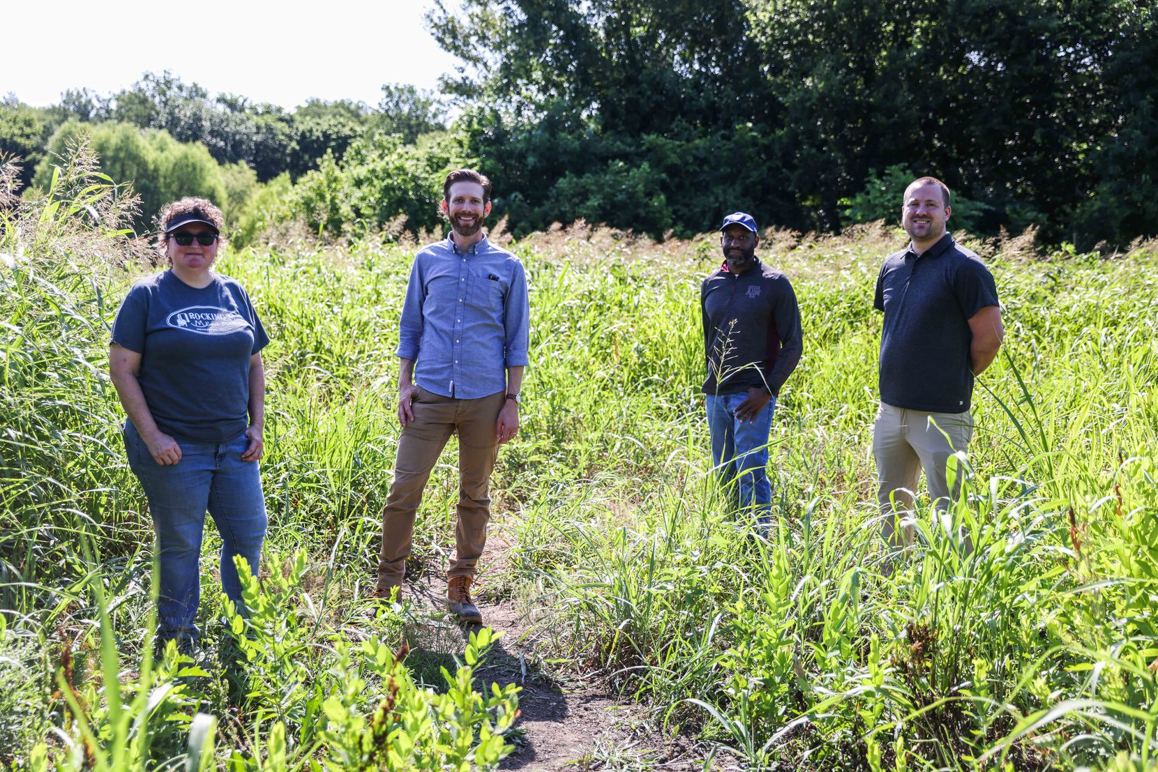 Casie Pierce (from left), a resident of the nearby Parkdale neighborhood and longtime trails advocate; Philip Hiatt Haigh, executive director of the Circuit Trail Conservancy; Allyn Media vice president Shawn Williams; and Kevin Oden of Dallas' Office of Integrated Public Safety Solutions, on a portion of the land south of Military Parkway that will become part of the Spine Trail's second phase.