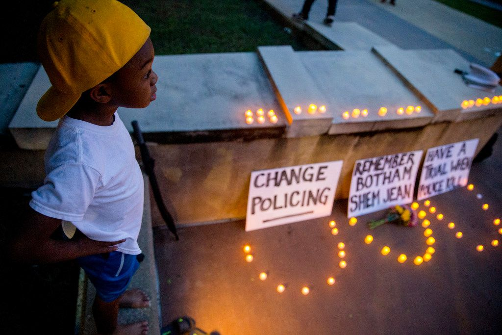 """""""Young King"""" Solomon Grayson, 6, stands on a ledge next to a memorial during a Mothers Against Police Brutality candlelight vigil for Botham Shem Jean at the Jack Evans Police Headquarters on Friday, Sept. 7, in Dallas. Botham Shem Jean was shot by a Dallas police officer who mistook his apartment for hers on Thursday night."""