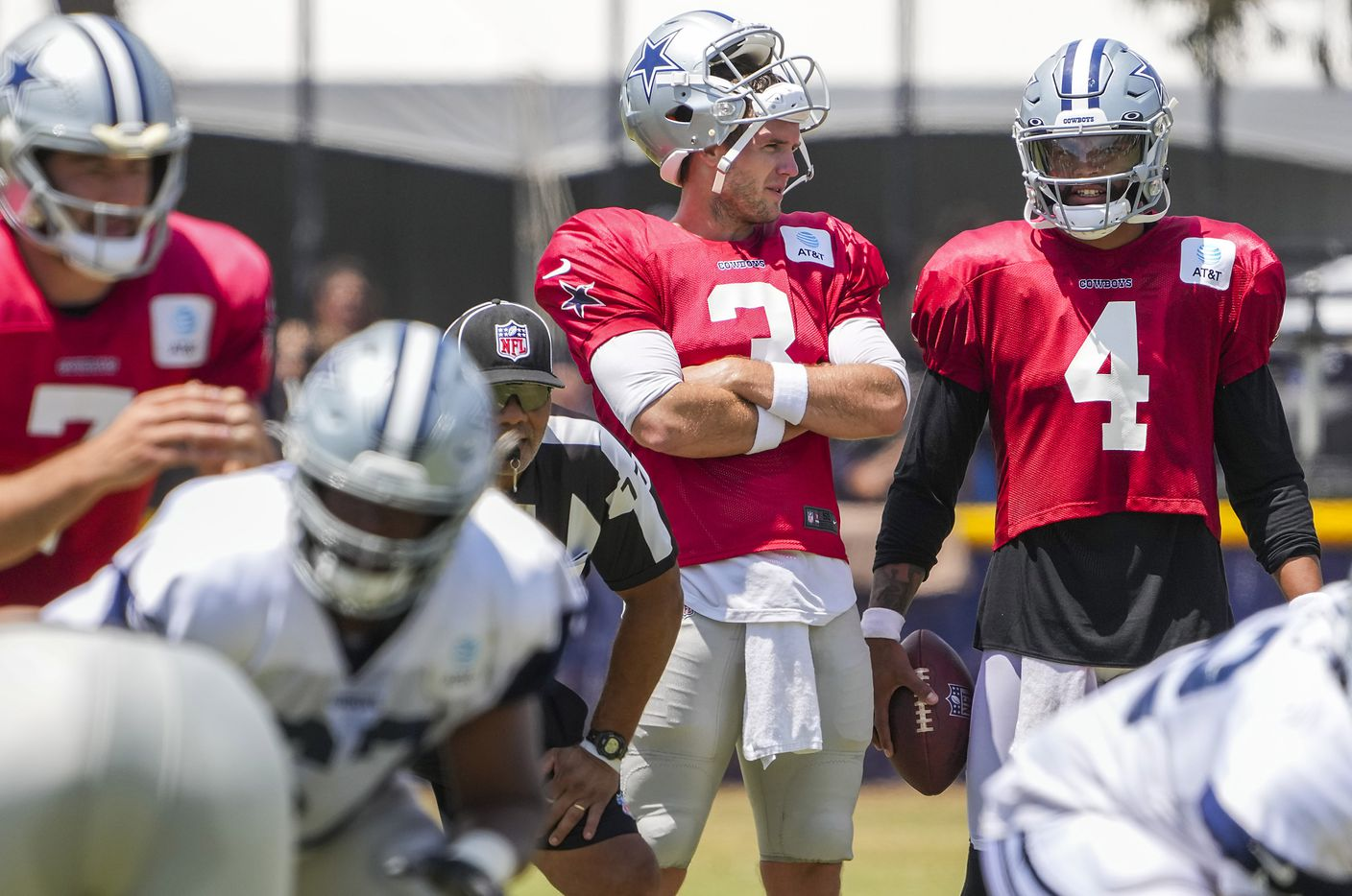 Dallas Cowboys quarterback Dak Prescott (4), who sat out of team drills, talks with quarterback Garrett Gilbert (3) as quarterback Ben DiNucci (7) takes a snap during a practice at training camp on Wednesday, July 28, 2021, in Oxnard, Calif.