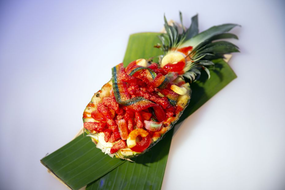 Rooftop bar 77 Degrees serves beachy food like this pineapple bowl filled with fruit, candy and Flamin' Hot Cheetos.