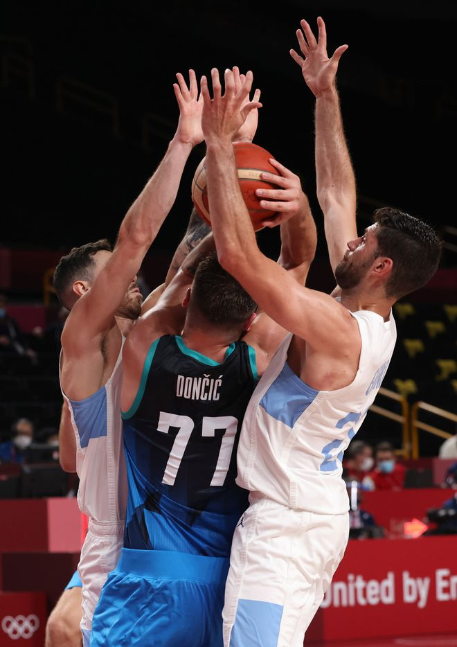 Slovenia's Luka Doncic (77) works his way out of a double team from Argentina's Luca Vildoza (17) and Patricio Garino (29) in the first half of play during the postponed 2020 Tokyo Olympics at Saitama Super Arena on Monday, July 26, 2021, in Saitama, Japan. Slovenia defeated Argentina 118-100. (Vernon Bryant/The Dallas Morning News)
