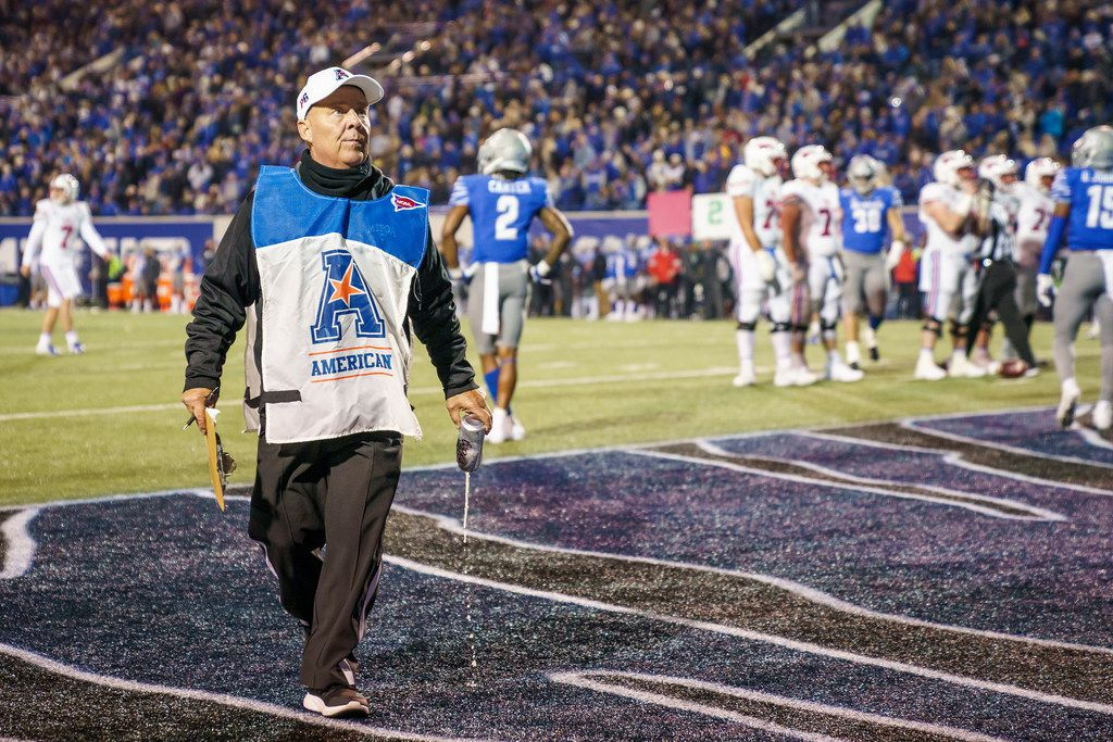 An official pours out a beer thrown on the field after a pass interference call went against Memphis during the second half of an NCAA football game against SMU at Liberty Bowl Memorial Stadium on Saturday, Nov. 2, 2019, in Memphis, Tenn. (Smiley N. Pool/The Dallas Morning News)