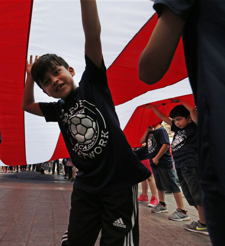 Youngsters help hold a large flag before the Mega March, which started at the Cathedral Shrine of Our Lady Guadalupe in downtown Dallas, photographed on Sunday, April 9, 2017. (Louis DeLuca/The Dallas Morning News)