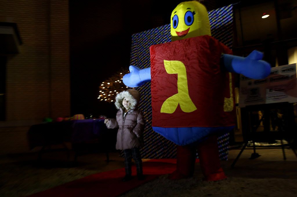 Children posed with a person dressed in a dreidel costume during Frisco's Hanukkah event.