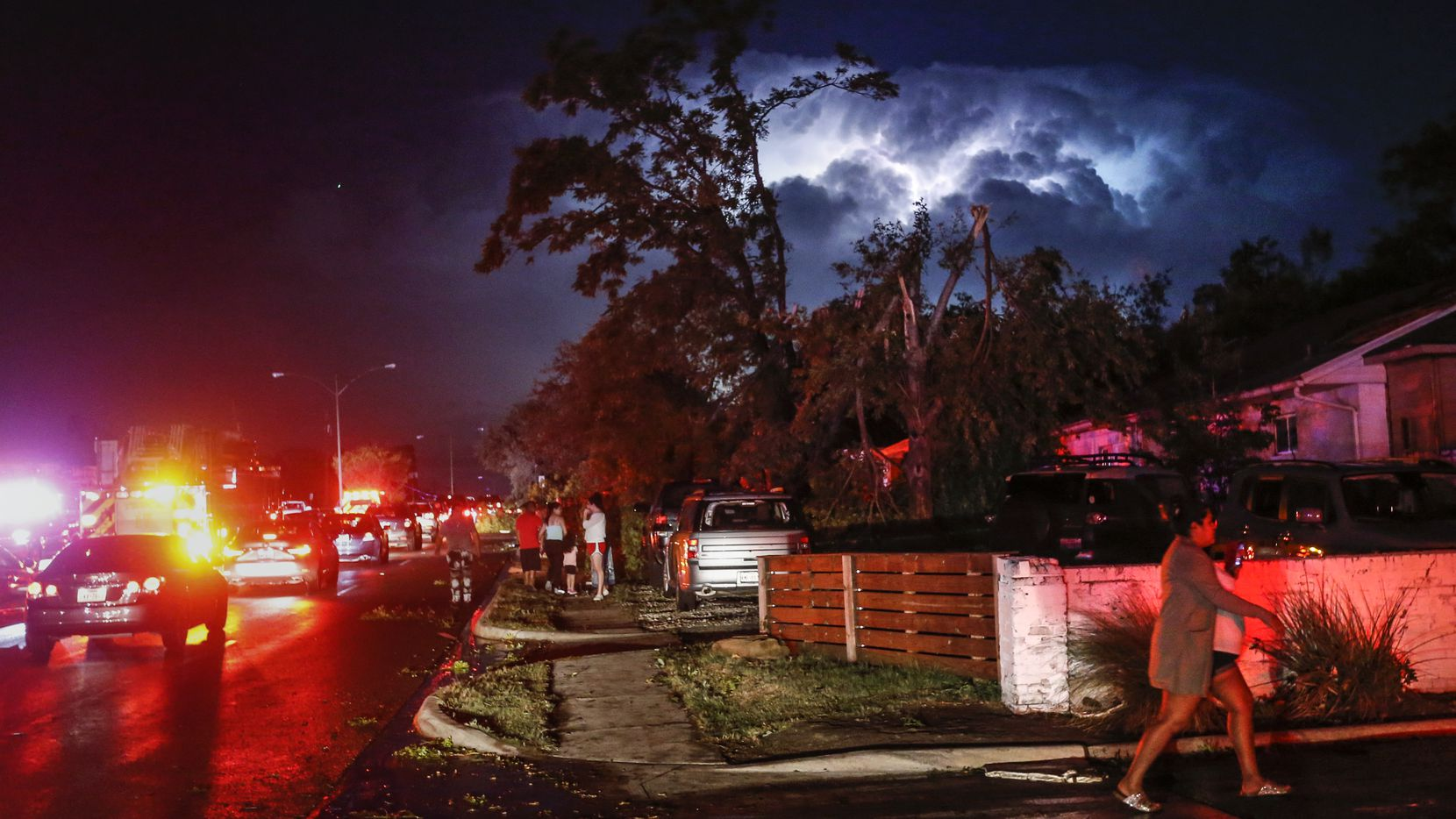 Lightning and emergency lights highlight damage as people gather in the parking lot of a shopping complex near the intersection of Walnut Hill Lane and Marsh Lane in Dallas where a tornado hit Sunday, Oct. 20, 2019.