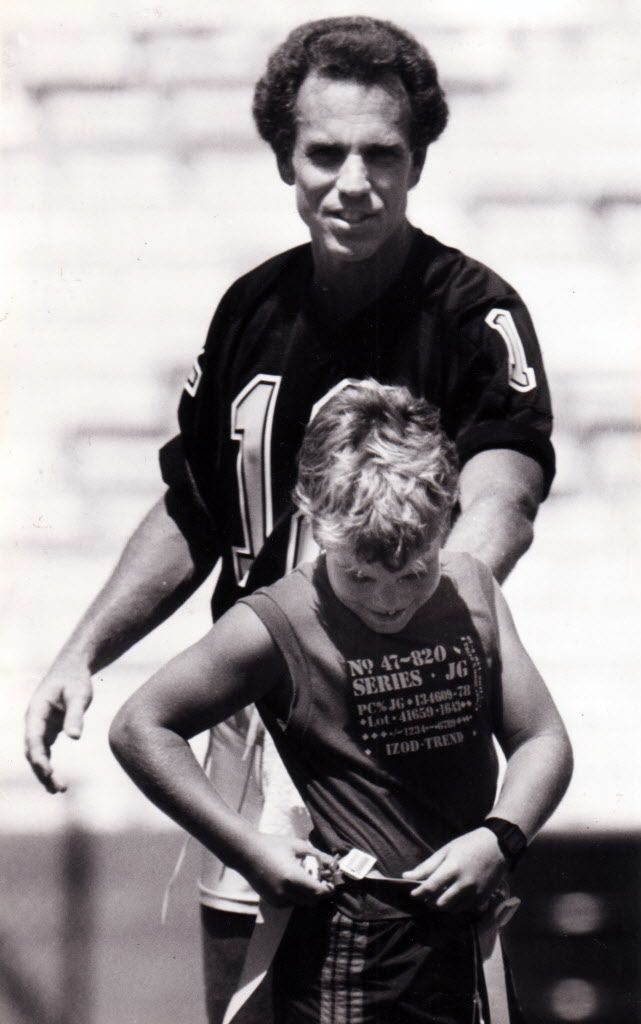 June 8, 1985 - In the 99-degree heat of the Cotton Bowl, former Dallas Cowboys tried to recapture their form of yesteryear in a game Saturday against sports writers, broadcasters and members of the Dallas Flag Football Association.  Here, Roger Staubach congratulates his son, Jeff, after he caught a pass.