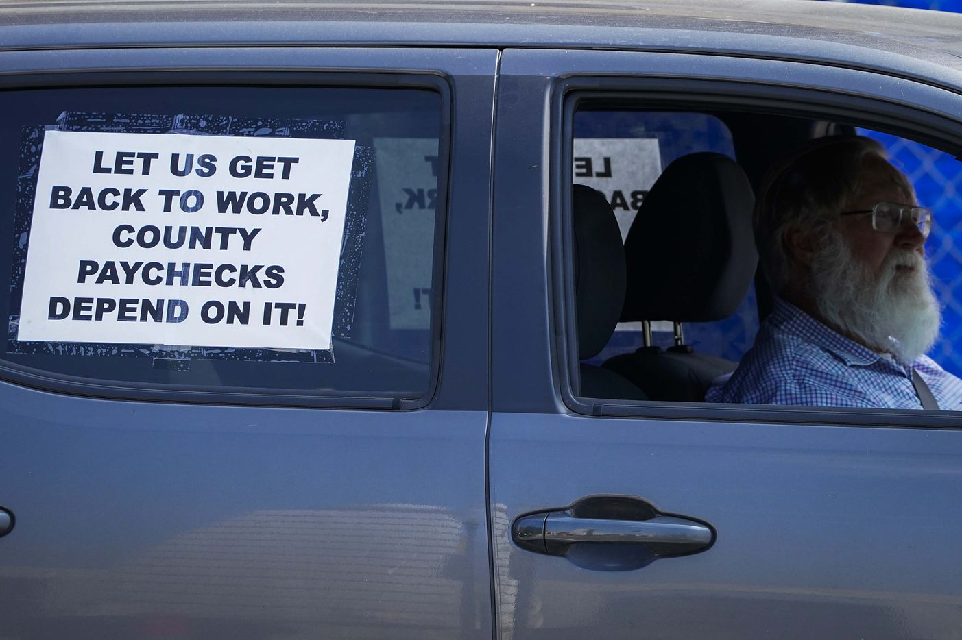 A driver passes by as protesters rally against government stay-at-home orders at Dealey Plaza on Tuesday, April 21, 2020, in Dallas.