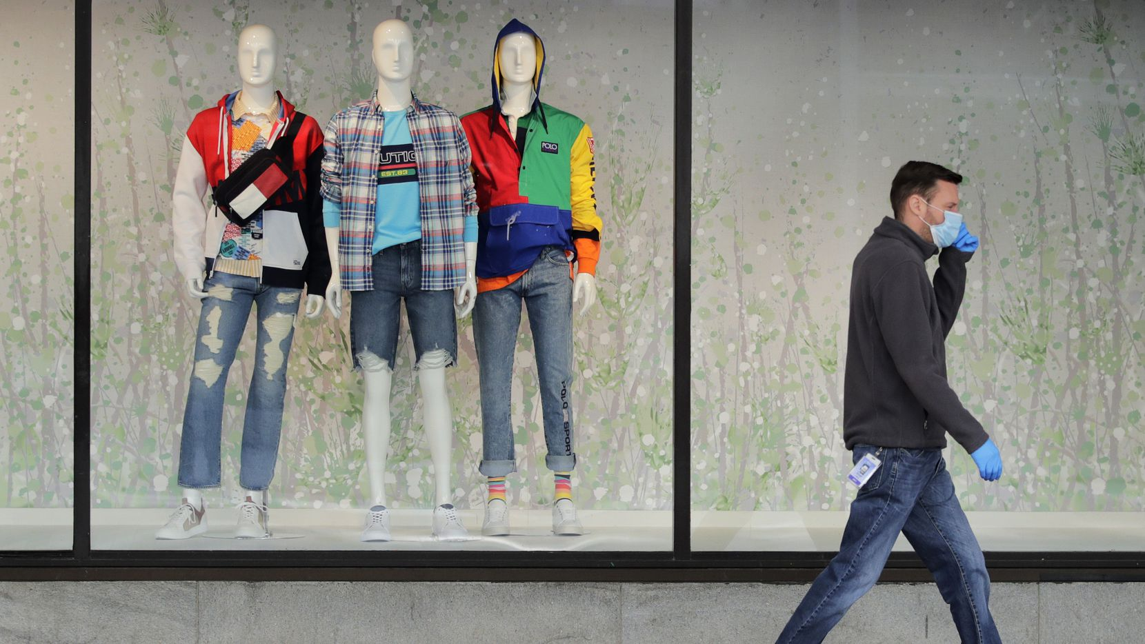 A man walks past mannequins in the windows of the Macy's store in Boston on April 15.
