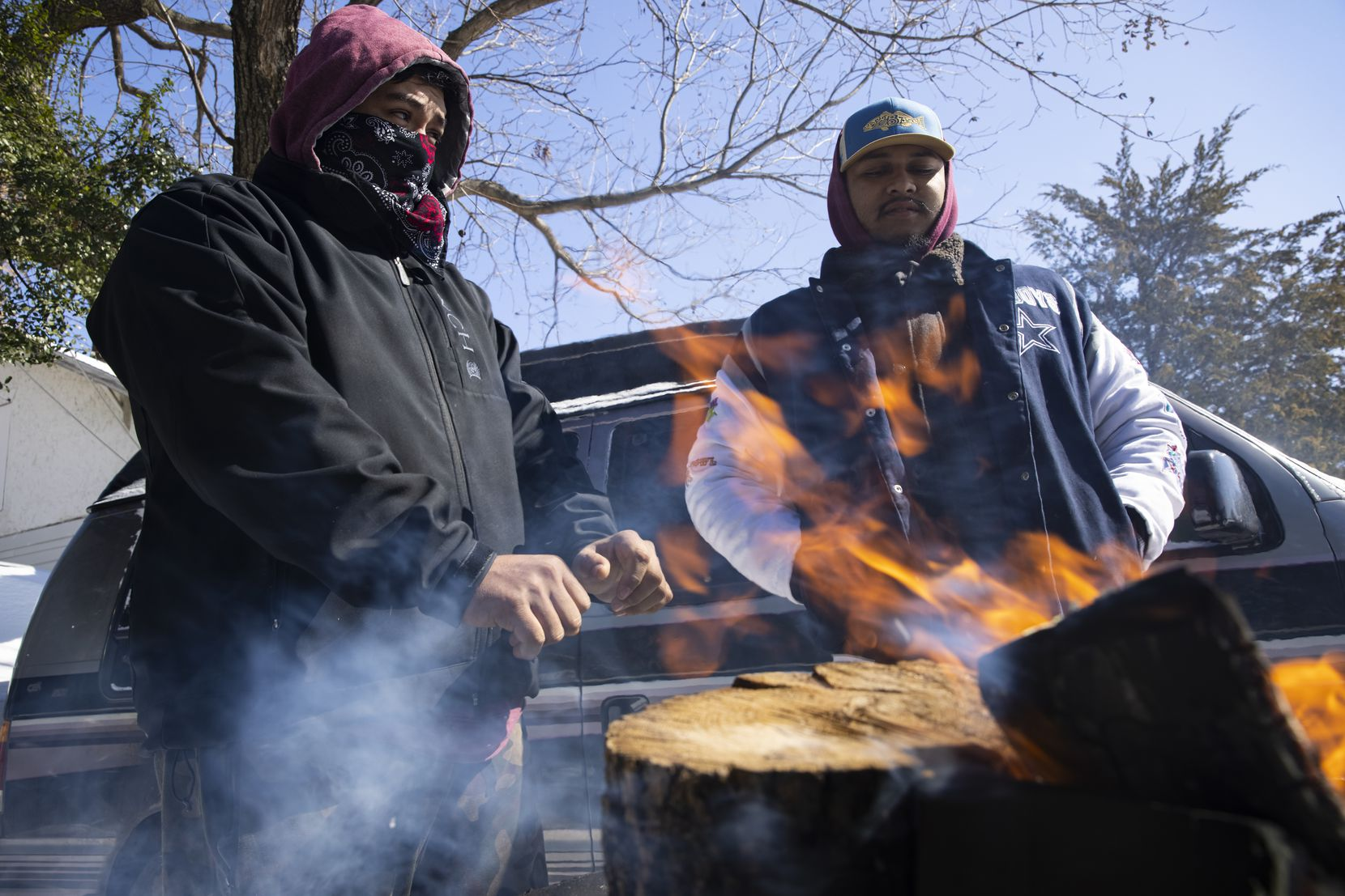 "(From left) brothers Alfredo Colon and Eduardo Colon chat over a fire in front of their East Dallas home on Monday, Feb. 15, 2021. The family lost their power during the night at around 2am. ""It feels better out here than it does in there,"" Alfredo said. (Juan Figueroa/ The Dallas Morning News)"