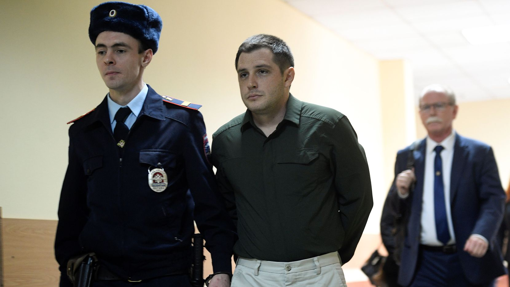 Police officers escort US ex-marine Trevor Reed, charged with attacking police, into a courtroom prior to a hearing in Moscow on March 11, 2020. (Photo by Alexander NEMENOV / AFP) (Photo by ALEXANDER NEMENOV/AFP via Getty Images)