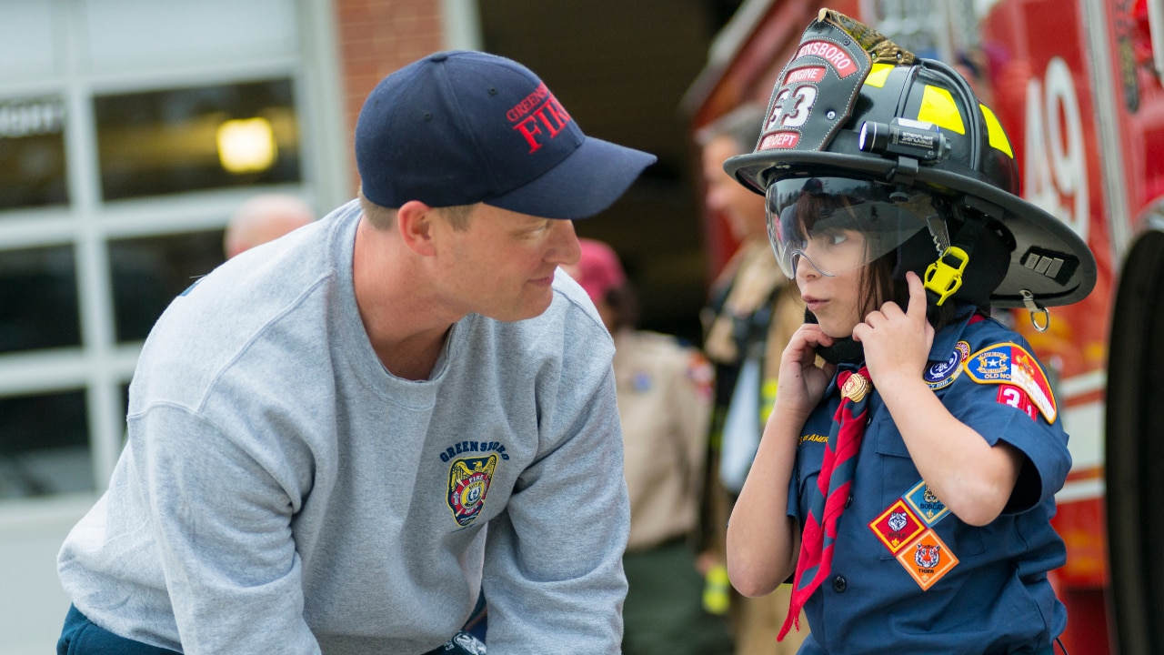 A young scout in uniform speaks with a firefighter and tries on his helmet.