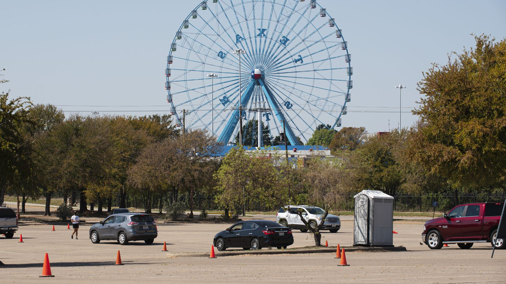 A few vehicles move towards the entrance of the State Fair of Texas Drive-Thru at Fair Park in Dallas, on Sunday, Oct. 11, 2020. To combat the large crowds and long lines, the State Fair of Texas has added additional staff and scanners to keep the lines at the entrance moving. Before 1pm on Sunday, State Fair staff scanned about 1,000 cars.